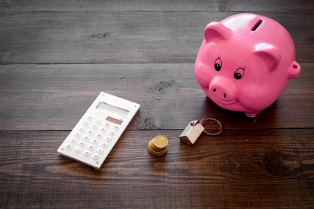 Mortgage. Savings for buy house. Moneybox in shape of pig near keychain in shape of car, coins, calculator on dark wooden background. Stock Photo