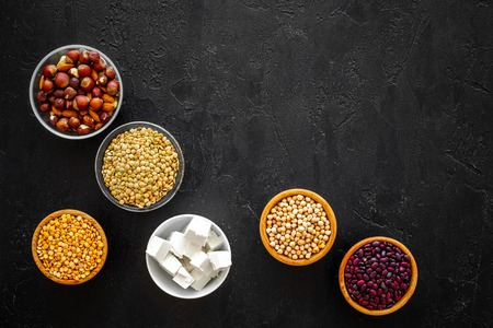 Products rich protein. Legumes, nuts, low-fat cheese. Raw beans, chickpeas, lentil, almond, hazelnut on black background top view