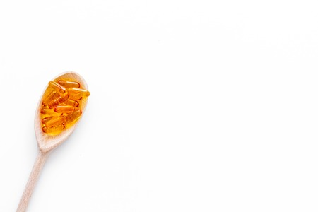 Reception of medicines concept. Pills in spoon on white background top view.