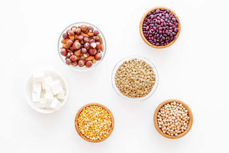 Vegan protein source. Legumes, nuts, cheese. Raw beans, chickpeas, lentil, almond, hazelnut on white background top view