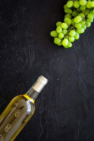 White wine in glass bottle near bunch of grapes on black background top view copy space Stockfoto