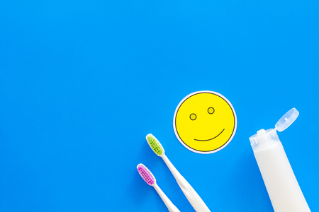 Teeth care, dental care. Toothbrushes and tooth paste near smile face emoji on blue background top view space for text