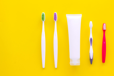 Teeth care, dental care. Toothbrushes and tooth paste on yellow background top view space for text