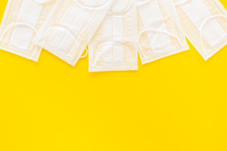 Flu prevention. Medical face masks on yellow background top view copy space Stock Photo
