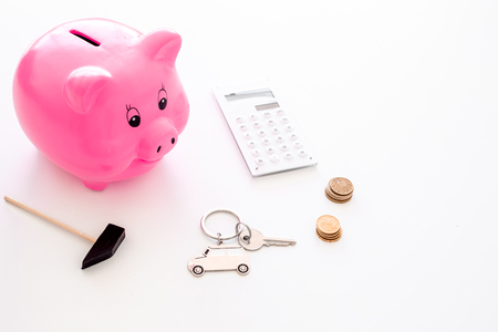 Money for buy car. Moneybox in shape of pig near keychain in shape of car, coins, calculator on white background copy space Foto de archivo - 106554406