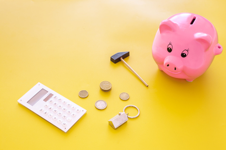 Mortgage. Savings for buy house. Moneybox in shape of pig near keychain in shape of car, coins, calculator on yellow background copy space Stockfoto