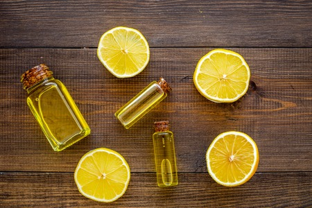 Natural cosmetics. Lemon essential oil near halfs os lemons on dark wooden background top view closeup Stock Photo