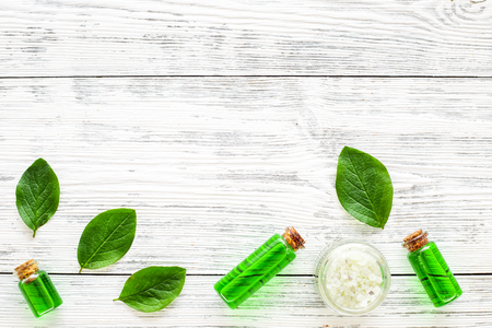 Natural hipoallergenic cosmetics with tea tree essential oil. Oil, lotion, leaves on white wooden background top view copy space