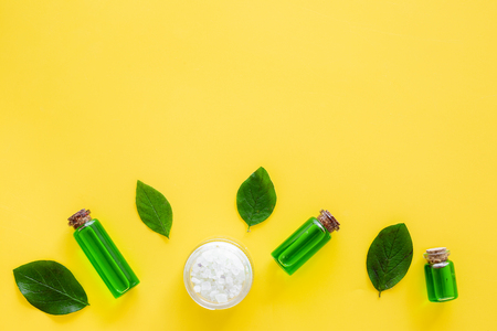 Natural hipoallergenic cosmetics with tea tree essential oil. Oil, lotion, leaves on yellow background top view copy space 스톡 콘텐츠