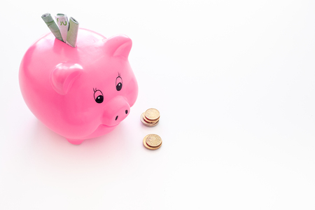 Savings. Moneybox in shape of pig with banknotes falling into it near coins on white background copy space Zdjęcie Seryjne
