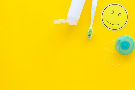 Set for daily teeth care. Toothbrush, tooth paste, dental floss on yellow background top view copy space