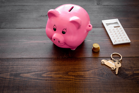 Money for buy car. Moneybox in shape of pig near keychain in shape of car, coins, calculator on dark wooden background copy space