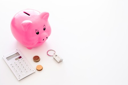 Mortgage. Savings for buy house. Moneybox in shape of pig near keychain in shape of car, coins, calculator on white background copy space Stockfoto