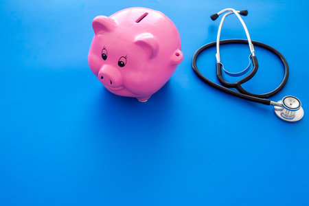 Money for treatment. Medical expenses. Moneybox in shape of pig near stethoscope on blue background copy space