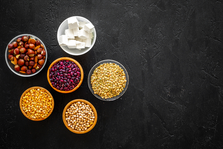Products rich protein. Legumes, nuts, low-fat cheese. Raw beans, chickpeas, lentil, almond, hazelnut on black background top view space for text