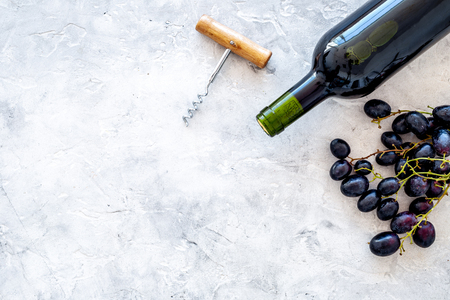 Red wine concept. Glass bottle with beverage near bunch of grapes and corkscrew on grey background top view space for text Banque d'images