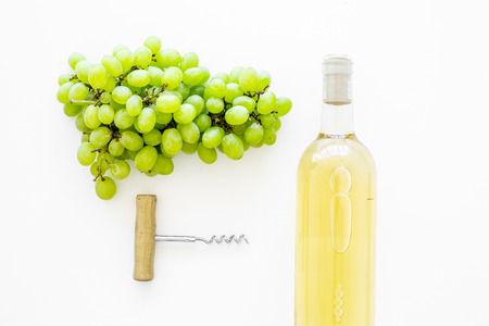 Open the wine concept. White wine in glass bottle near bunch of grapes and corkscrew on white background top view.