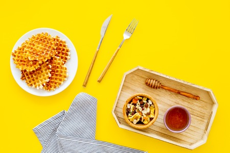 Round belgian waffles for breakfast. Breakfast in bed. Waffles on plate. Honey and dried fruits in tray, knife and fork, tablecloth on yellow background top view. Stock Photo