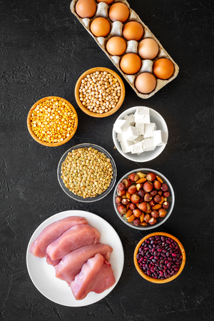 Food for sportsmen. Legumes, nuts, low-fat cheese, meet, eggs on black background top view.