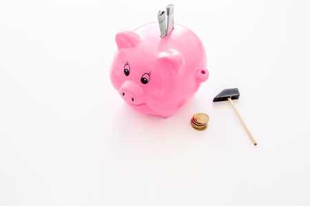 Savings. Moneybox in shape of pig with banknotes falling into it near coins on white background. 스톡 콘텐츠