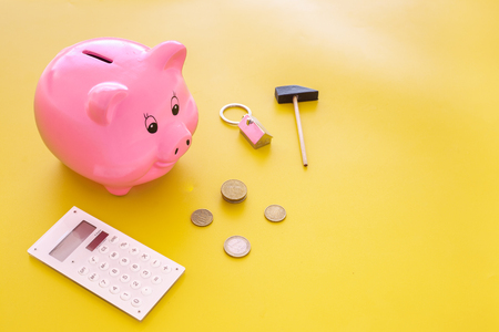 Mortgage. Savings for buy house. Moneybox in shape of pig near keychain in shape of car, coins, calculator on yellow background.