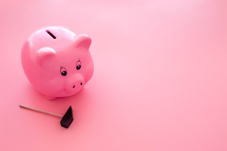 Piggy bank. Moneybox in shape of pig near hammer on pink background. 스톡 콘텐츠