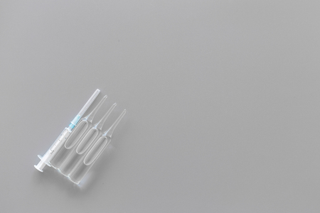 Flu vaccination concept. Syringe and ampoulie on grey background top view. Stock Photo