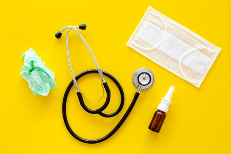 Flu drops. Running nose concept. Wrinkled napkin near stethoscope and face mask on yellow background top view. Imagens
