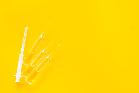 Flu vaccination concept. Syringe and ampoulie on yellow background top view.