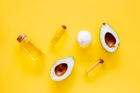 Cosmetics for skin care. Avocado oil near half of avocado on yellow background top view.