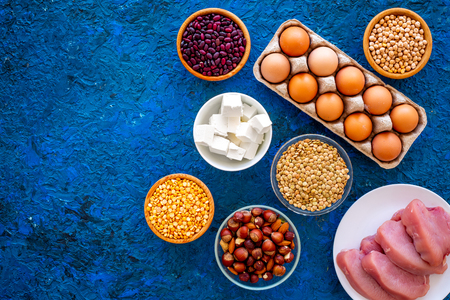 Food for sportsmen. Legumes, nuts, low-fat cheese, meet, eggs on blue background top view.