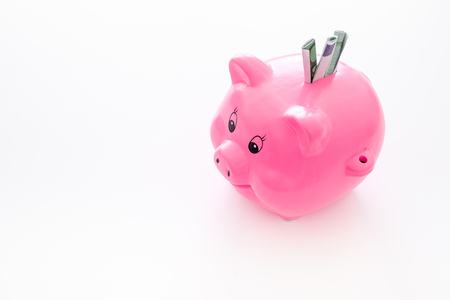 Savings. Moneybox in shape of pig with banknotes falling into it on white background.