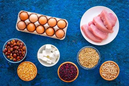Food for sportsmen. Legumes, nuts, low-fat cheese, meet, eggs on blue table top view.