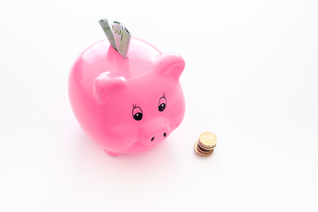 Savings. Moneybox in shape of pig with banknotes falling into it near coins on white background. Stok Fotoğraf