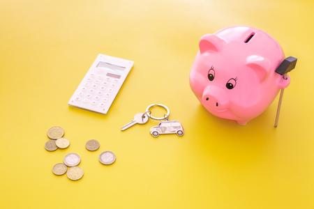 Money for buy car. Moneybox in shape of pig near keychain in shape of car, coins, calculator on yellow background.
