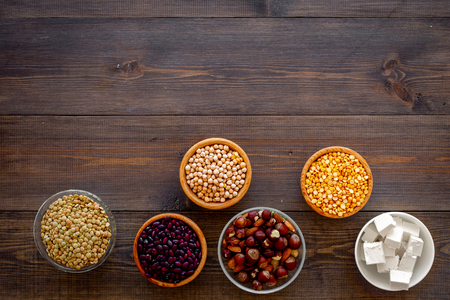 Vegan protein source. Legumes, nuts, cheese. Raw beans, chickpeas, lentil, almond hazelnut on dark wooden background top view Stock Photo