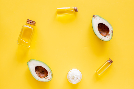 Cosmetics for skin care. Avocado oil near half of avocado on yellow background top view. 스톡 콘텐츠 - 106732266