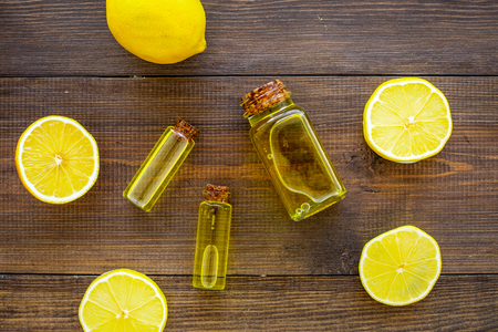 Natural cosmetics. Lemon essential oil near halfs os lemons on dark wooden background top view.