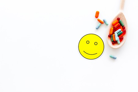 Reception of medicines concept. Pills in spoon near smile face emoji on white background top view. Stock Photo