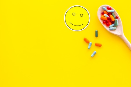 Reception of medicines concept. Recovery. Pills in spoon near smile face emoji on yellow background top view.