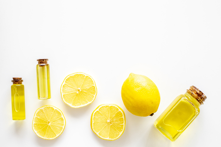 Natural cosmetics. Lemon essential oil near halfs os lemons on white background top view closeup space for text Stock Photo