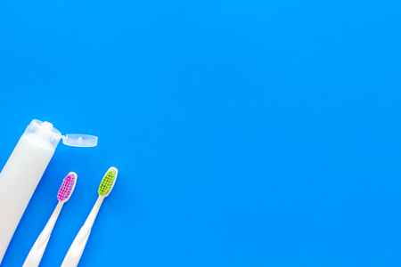 Teeth care, dental care. Toothbrushes and tooth paste on blue background top view space for text