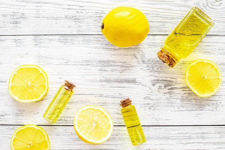Organic cosmetics with natural ingredients. Lemon essential oil near halfs os lemons on white wooden background top view closeup copy space