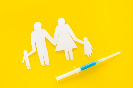 Vaccination for healthy family, vacctination of children. Flu. Syringe near family cutout on yellow background top view space for text