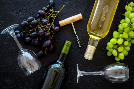 Composition with wine bottles. Red and white wine bottles, bunch of grapes, corkscrew, wine glasses on black background top view. Stockfoto