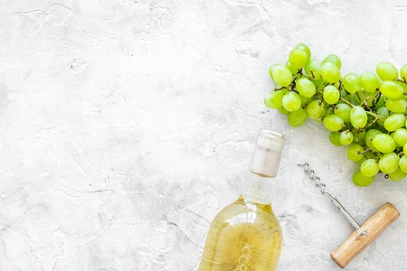Open the wine concept. White wine in glass bottle near bunch of grapes and corkscrew on grey background top view.