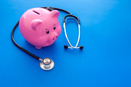 Money for treatment. Medical expenses. Moneybox in shape of pig near stethoscope on blue background.