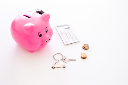Money for buy car. Moneybox in shape of pig near keychain in shape of car, coins, calculator on white background. Foto de archivo - 106789014