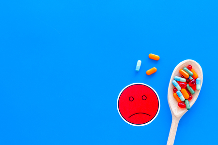 Illness. Drug intake. Pills in spoon near sad face emoji on blue background top view.