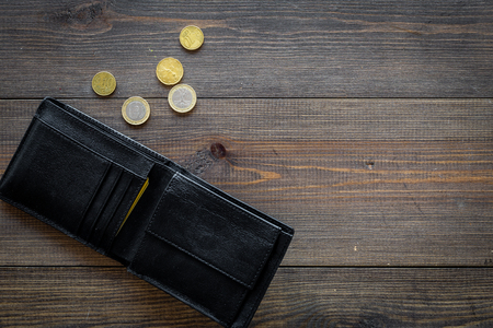 Unemployment concept. Lack of money. Coins fall out of wallet on dark wooden background top view.